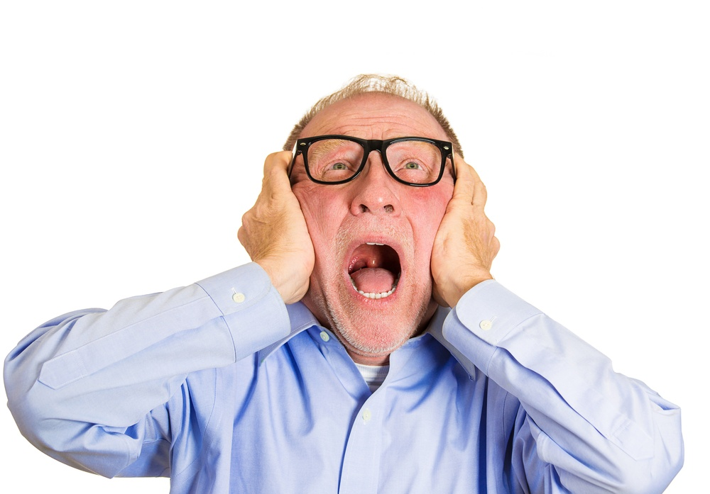 Closeup portrait, angry senior man, nerd black glasses, covering ears, looking up, to say, stop making that loud noise it's giving me a headache, isolated white background. Negative human emotion